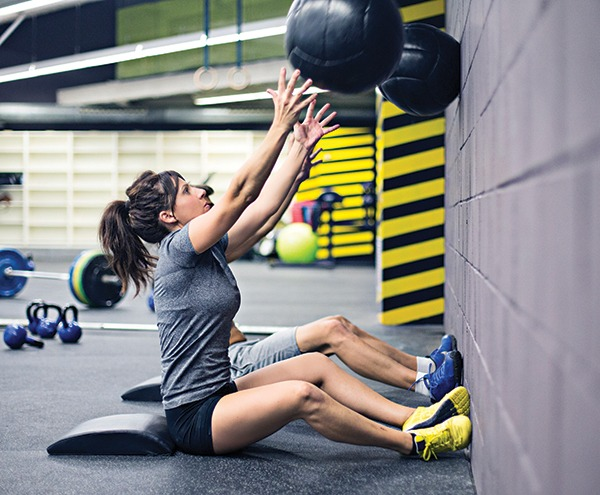 Woman throwing medicine ball against wall with TREAD Grip flooring